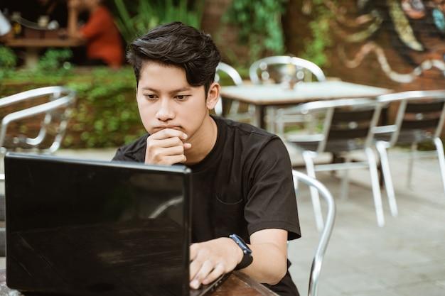 Grave jeune homme à l'aide d'un ordinateur portable