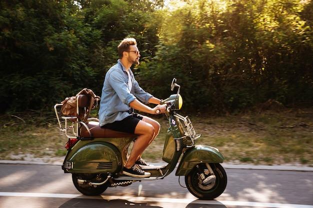 Grave jeune homme barbu sur scooter à l'extérieur.