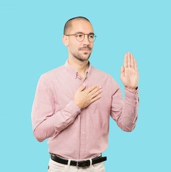 Grave jeune homme avec un geste de serment