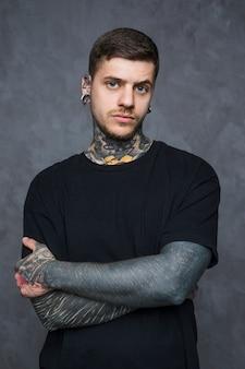 Grave jeune homme tatoué avec piercing dans les oreilles et le nez en regardant la caméra
