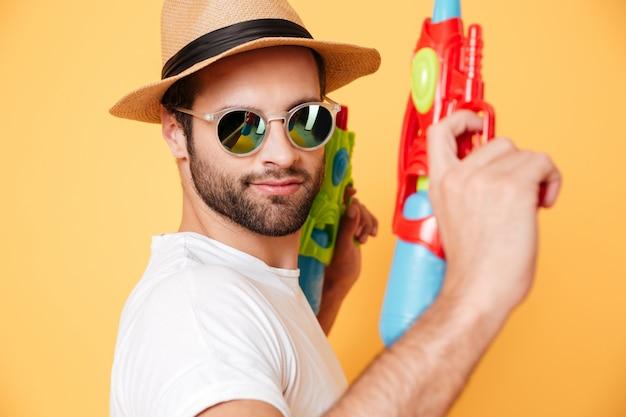 Grave jeune homme tenant des pistolets à eau jouets