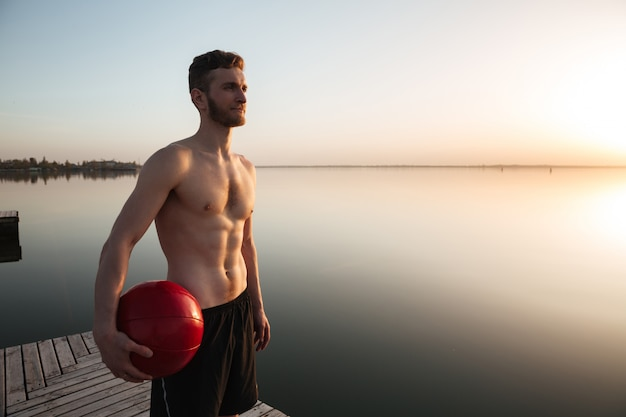 Grave jeune sportif debout avec ballon à la plage.