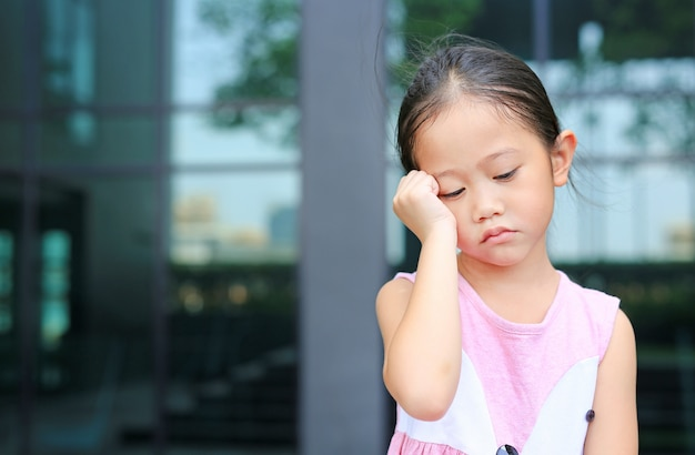 Grave petite fille avec posture sa main sur la joue