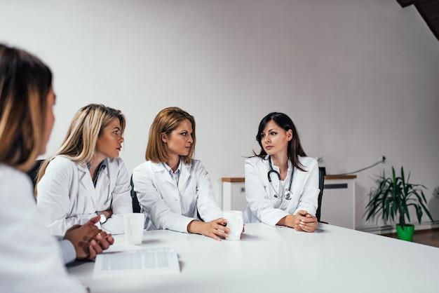 Graves médecins femmes discutant de diagnostic tout en restant assis à la table.