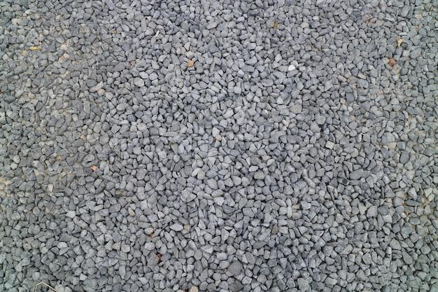 Gravier gris sur le sol dans le parc. concept d'arrière-plan. flou artistique.