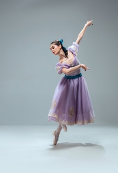 Gravité zéro. belle danseuse de salon contemporaine isolée sur mur gris. artiste professionnel sensuel dansant la valse, le tango, le slowfox et le quickstep. flexible et léger.