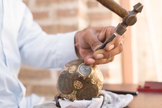 Gravure artisanale de motifs sur la verseuse. maîtres d'asie centrale. monnayage manuel du cuivre