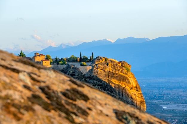 Grèce. coucher de soleil d'été dans les météores. monastère de roche sur le fond des crêtes et de la vallée de montagne