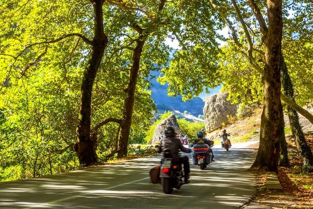 Grèce. journée ensoleillée d'été à l'ombre de la forêt sur une route de montagne. groupe de touristes à moto