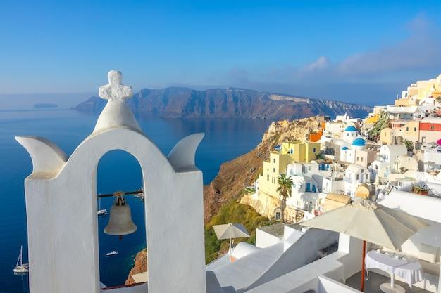 Grèce. une journée ensoleillée à santorin. cloche d'église et terrasses d'hôtel à oia