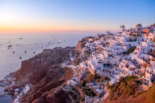 Grèce. maisons blanches et toits de l'île de santorin (thira). de nombreux bateaux avec des touristes partent en mer pour rencontrer le coucher du soleil