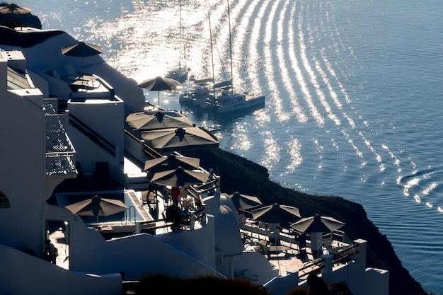 Grèce. soirée à la caldeira de santorin. maisons et terrasses à contre-jour du soleil. voiliers au mouillage