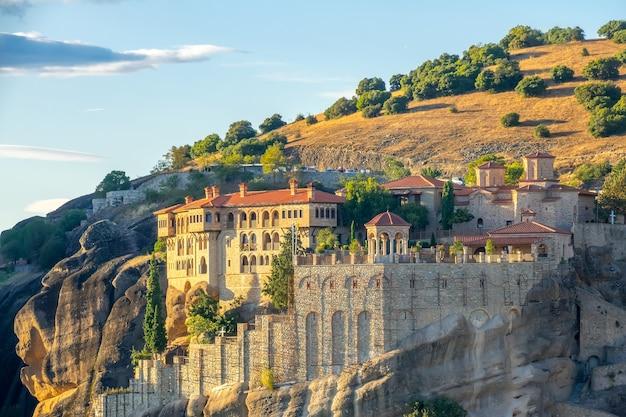 Grèce. soirée d'été ensoleillée à meteora. grand monastère en pierre sur un rocher