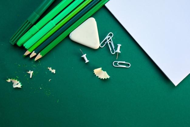 Green flat lay concept de retour à l'école, fournitures scolaires et de bureau avec espace de copie. beaucoup d'articles de papeterie différents sur fond coloré