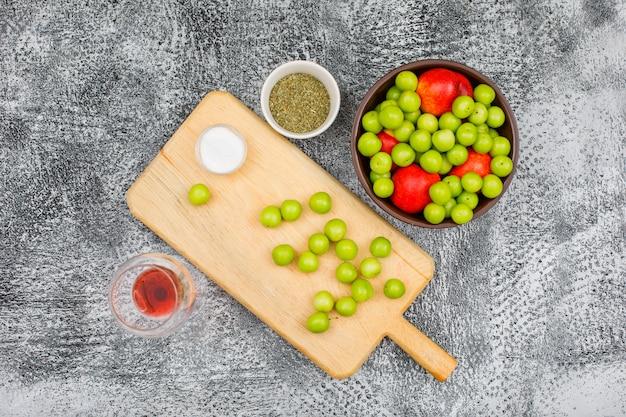 Greengages et pêches avec une petite barre de sel et de thym frotté séché, un verre de vin rouge dans un bol brun et une planche à découper sur grunge, vue du dessus