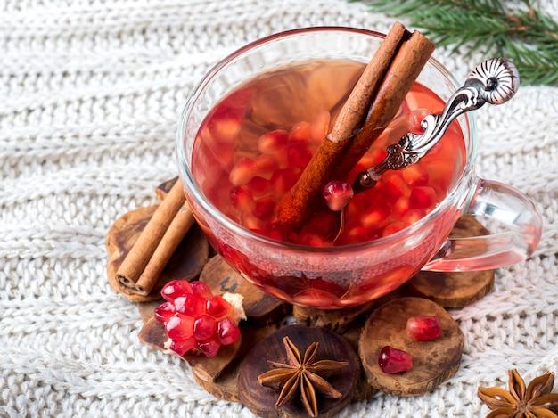 Grenade mûre fraîche et vin rouge dans une tasse en verre sur une couverture tricotée blanche