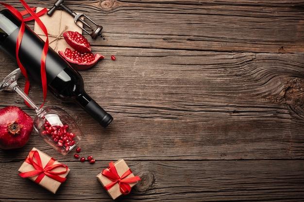 Grenade mûre avec un verre de vin, une bouteille et un cadeau sur un fond en bois