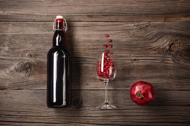 Grenade mûre avec un verre de vin, une bouteille sur un fond en bois