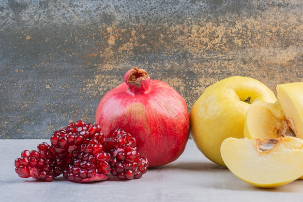 Grenade et pomme fraîches, sur le marbre.