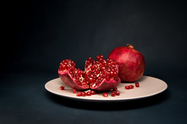 Grenade rouge sur une assiette sur une surface sombre