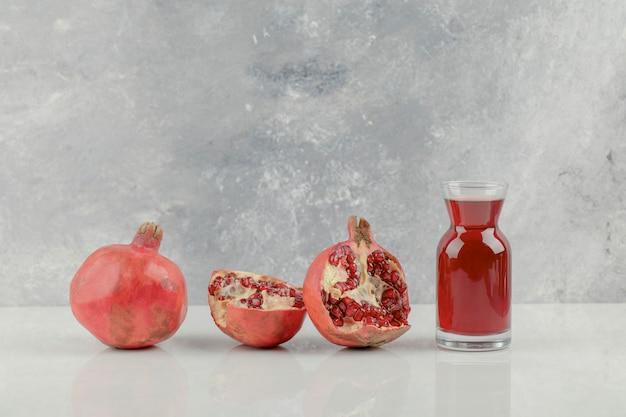 Grenades fraîches rouges et jus de fruits frais sur tableau blanc.