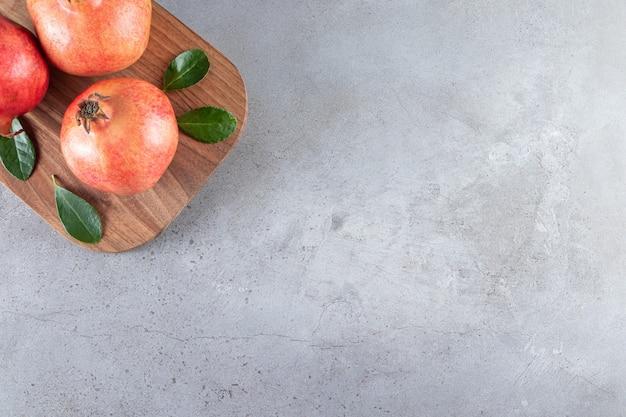 Grenades mûres fraîches avec des feuilles vertes sur une planche à découper en bois.