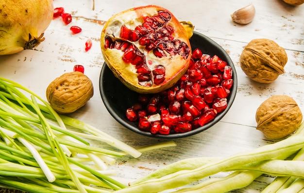Grenades mûres; noyer; oignon de printemps; et haricots sur table en bois