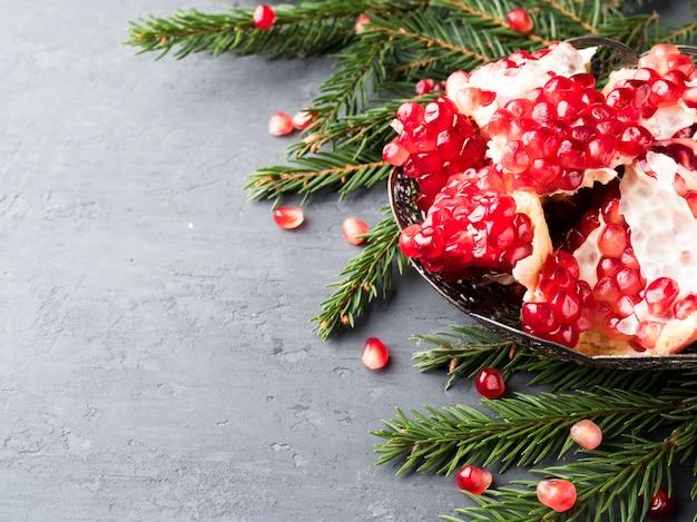 Grenat rouge juteux pelé dans une assiette vintage sur un arbre de noël