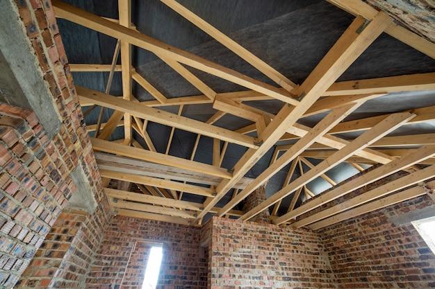 Grenier d'un immeuble en construction avec poutres en bois d'une structure de toit et murs de briques. concept de développement immobilier.