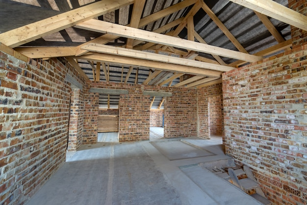 Grenier d'un immeuble en construction avec poutres en bois d'une structure de toit et murs de briques.