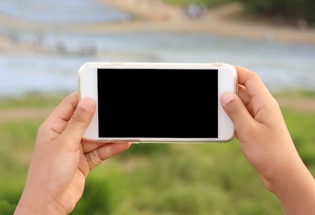 Un gril mains tenant un téléphone intelligent à écran tactile noir vide au parc en plein air.