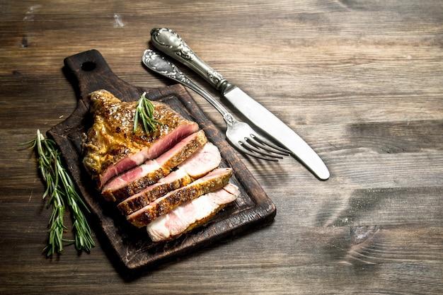 Grill de boeuf aux épices sur une planche à découper. sur une table en bois.