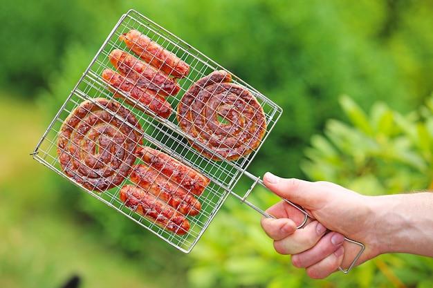 Grill saison. saucisses frites au bacon dans une main masculine sur vert