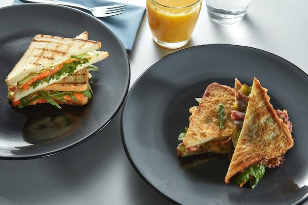 Grill sandwich et pain grillé pour le petit déjeuner avec du jus d'orange sur la table