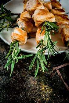 Grill, viande de barbecue. brochettes de poulet au romarin. sur un métal rouillé noir, vue de dessus