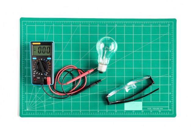 Grille de coupe verte mat ou pad avec outil de travail voltmètre en arrière-plan.