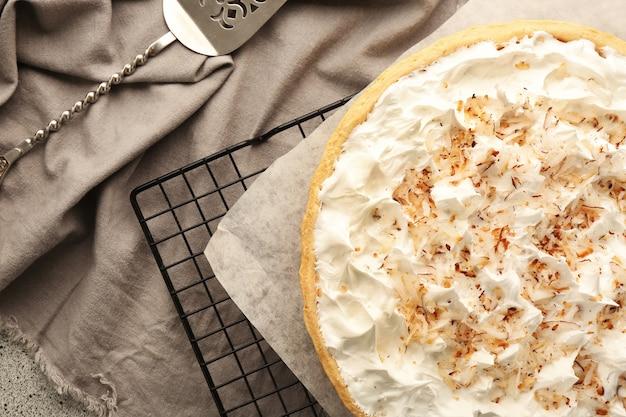 Grille avec une délicieuse tarte à la crème de noix de coco sur une table grise