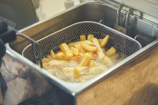Grille avec des lanières de pomme de terre descendues dans l'huile bouillante