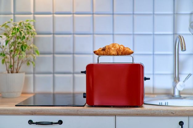 Grille-pain rouge moderne réchauffer un croissant sucré brun