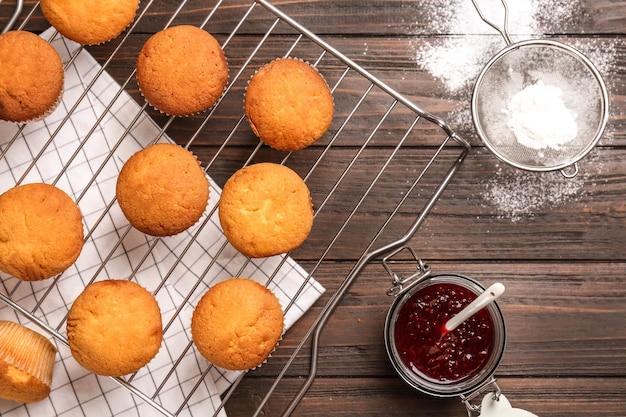 Grille de refroidissement avec de savoureux petits gâteaux, pot de confiture et sucre en poudre sur la table.