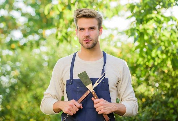 Griller les aliments. ustensiles de barbecue. cuisiner des hamburgers. l'homme tient l'équipement de barbecue. week-end d'été. outils pour rôtir la viande à l'extérieur. soirée barbecue. notion de pique-nique. chef de barbecue. beau mec cuisiner de la nourriture.