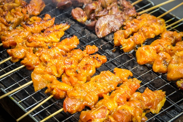 Griller le poulet barbecue sur le feu