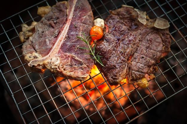 Griller t bone steak sur la grille flamboyante