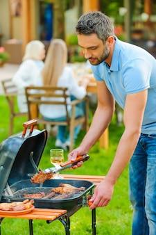 Griller la viande à la perfection. jeune homme confiant faisant griller de la viande sur le gril tandis que d'autres membres de la famille sont assis à la table à manger en arrière-plan