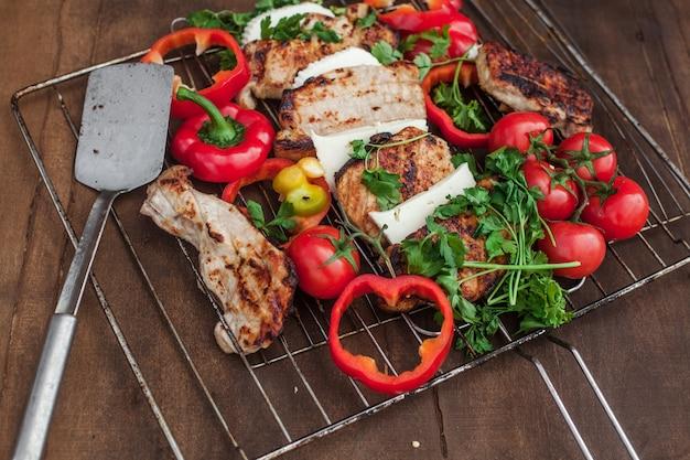 Griller avec de la viande prête, du fromage et des légumes rouges sur une table en bois