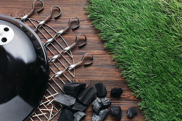 Grilles grillagées avec brochette métallique et charbon sur bois texturé