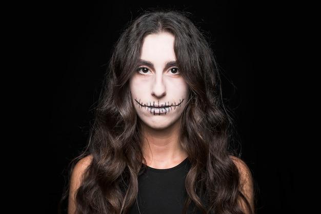 Grim jeune femme avec le maquillage de l'épouvantail