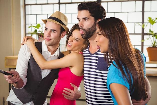 Grimaçant des amis prenant des selfies avec selfiestick
