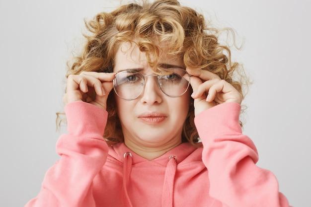 Grimaçant fille confuse mis des lunettes, fronçant les sourcils perplexe