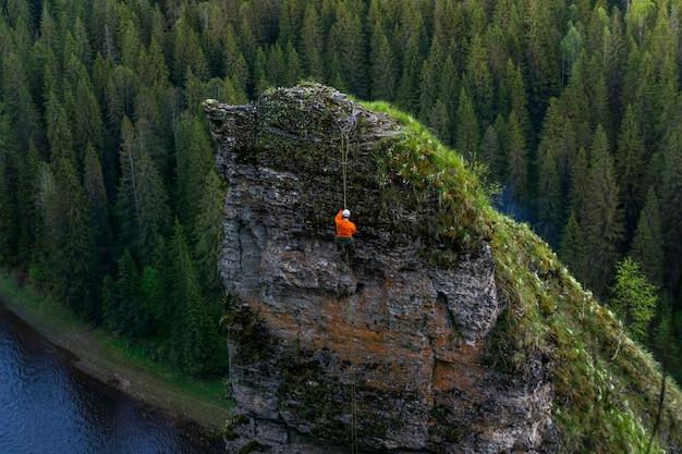 Le grimpeur descend du haut d'une falaise abrupte au-dessus de la rivière